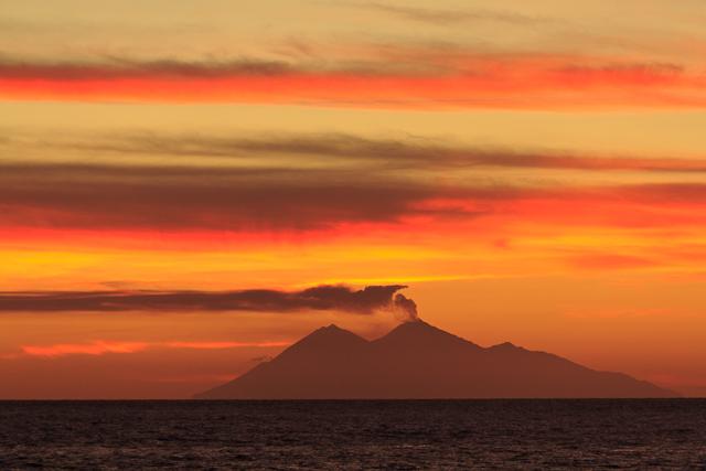 Atemberaubender Sonnenuntergang mit rauchendem Vulkan