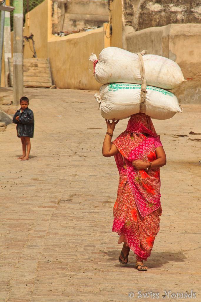 Indische Frau mit eine schweren Last auf dem Kopf in Mandawa